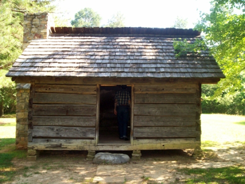 Lower class Cherokee home - one small room consisting of one bed, 2 gourd bowls, a grinding log for meal, one deer skin, and a gourd ladle