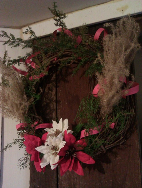 Our vine wreath decorated with evergreen twigs, red paper, scrub grass puffs, and old artificial flowers.